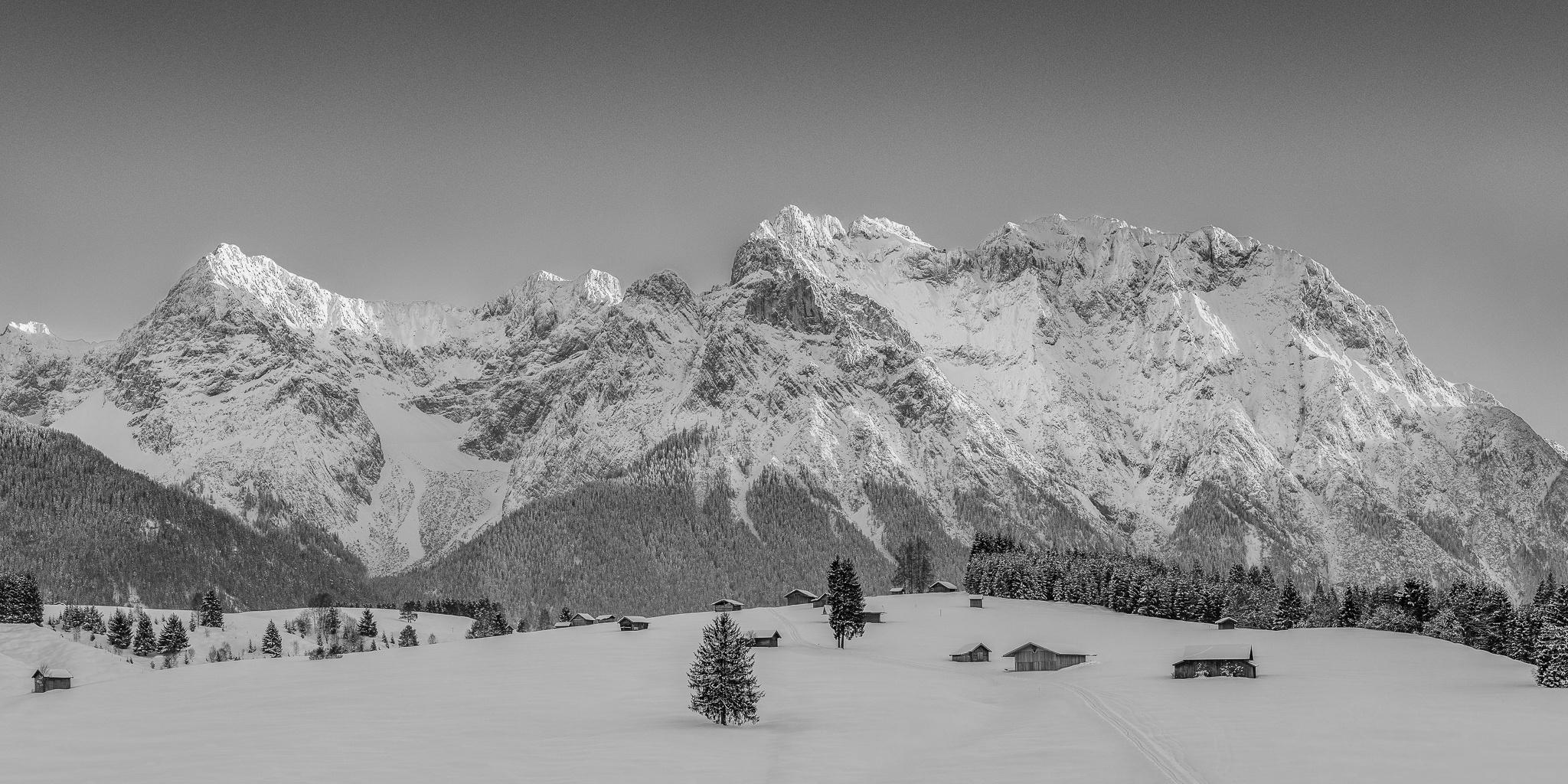 Bei einer Wanderung auf den Buckelwiesen von Klais Richtung Krün hat man immer wieder die Westliche Karwendelspitze im Blick. Winter - Berglandschaft schwarz weiß.
