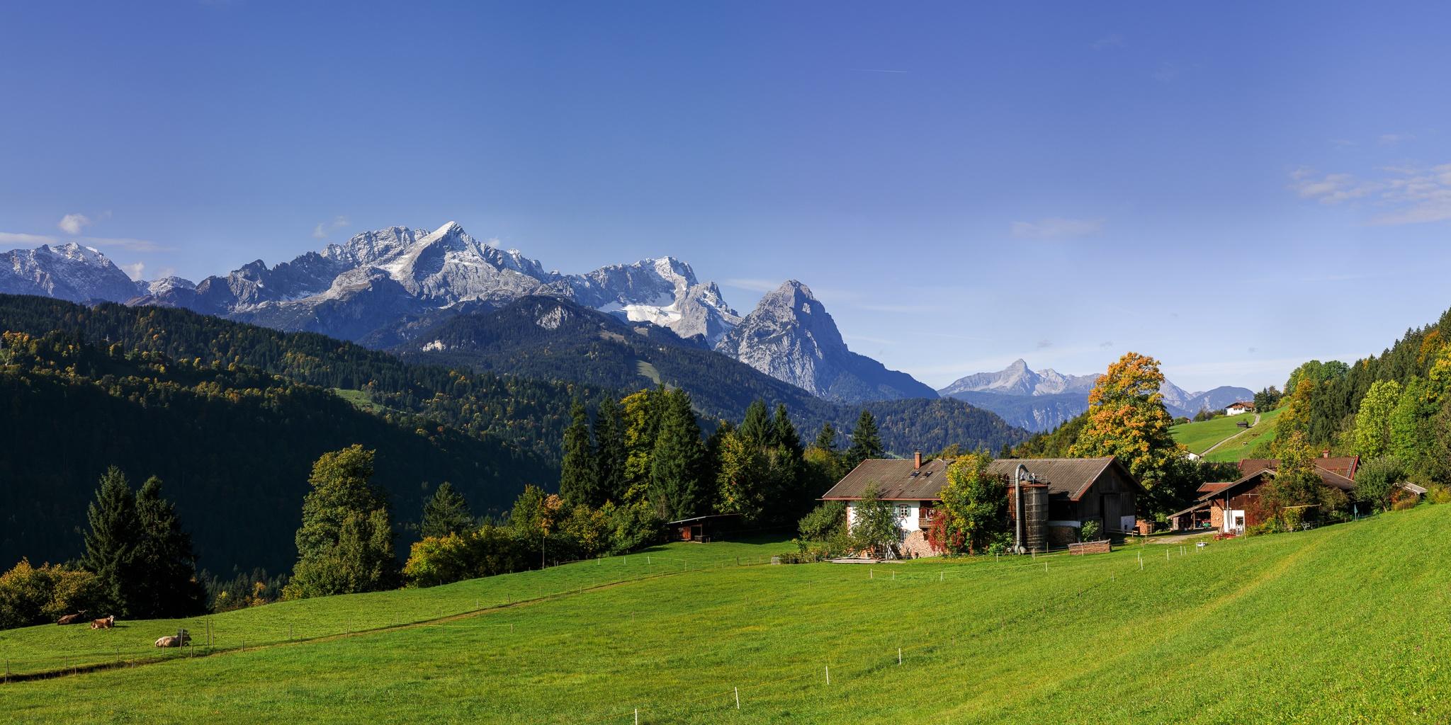 Bergbauernhof mit Blick auf die Garmisch-Partenkirchener Berge bei Sonnenaufgang.