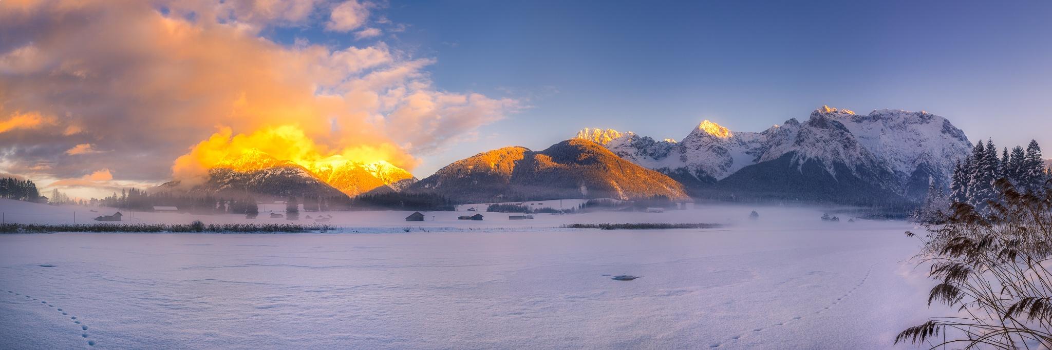 Winter und Abendrot. Traumhafter Winterabend am Schmalensee, Pulverschnee auf den Bäumen und die Abendsonne erleuchtet spektakulär die Wolken am Soierngebirge.