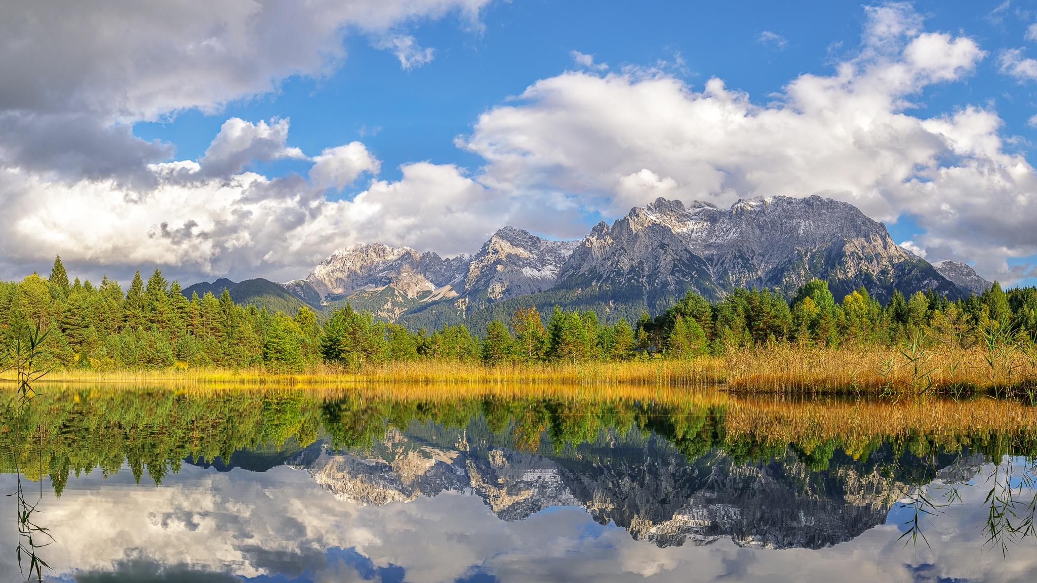 Wolkenspiel über dem Karwendelgebirge. Der Luttensee liegt idyllisch in einer Senke oberhalb von Mittenwald. Spiegelbild vom Mittenwalder Karwendelgebirge im Luttensee.